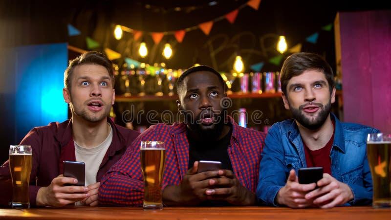 друзья Смешанн-гонки сравнивая номера лотереи по телевизору в баре с онлайн билетами стоковые изображения