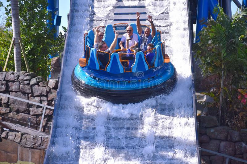 Друзья смеются перед выдерживать в привлекательности воды на тематическом парке Seaworld морском стоковое фото rf