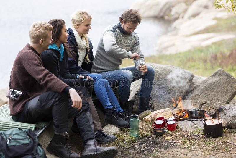 Друзья смотря кофе человека меля на месте для лагеря стоковая фотография