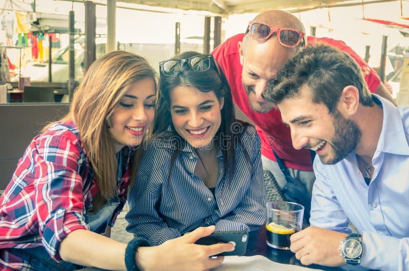 Друзья смотря мобильный телефон в баре стоковая фотография