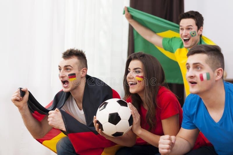 Друзья смотря футбольную игру на ТВ стоковые фото