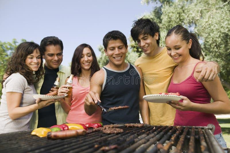 Друзья собранные вокруг гриля на пикнике стоковая фотография rf