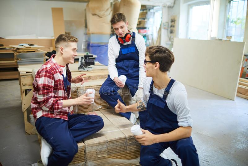 Друзья содержания деля новости на перерыве в магазине плотничества стоковая фотография rf