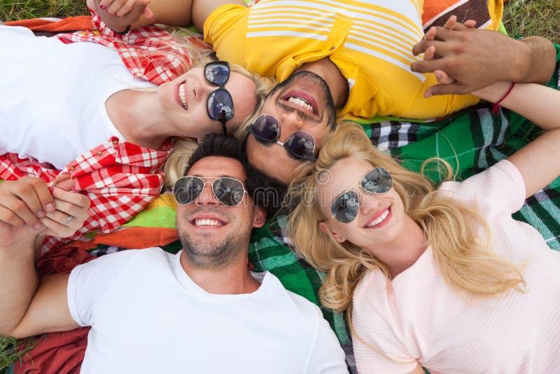 Друзья счастливой группы людей молодые лежа вниз на одеяле пикника внешнем стоковые фотографии rf