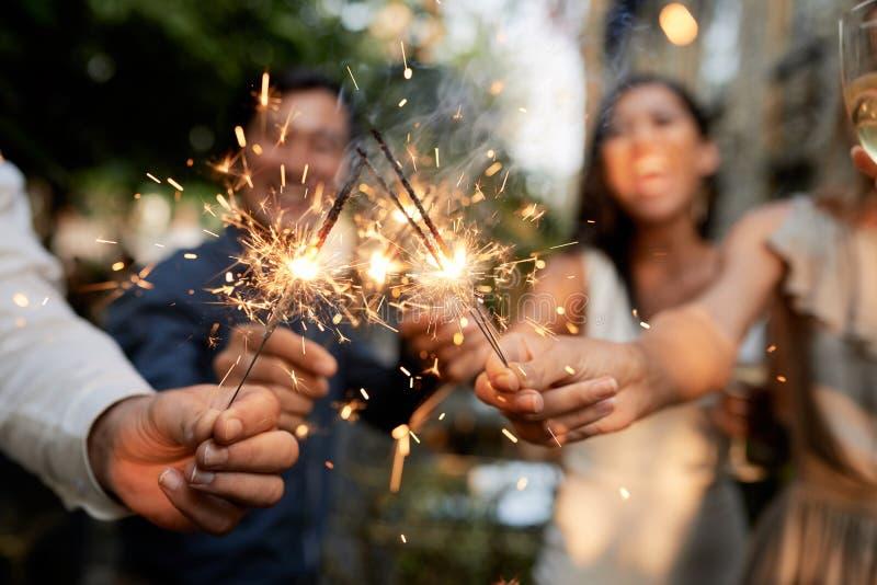 Друзья с горящими бенгальскими огнями стоковая фотография rf
