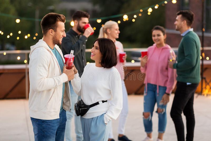 Друзья с напитками в чашках партии на крыше стоковое изображение