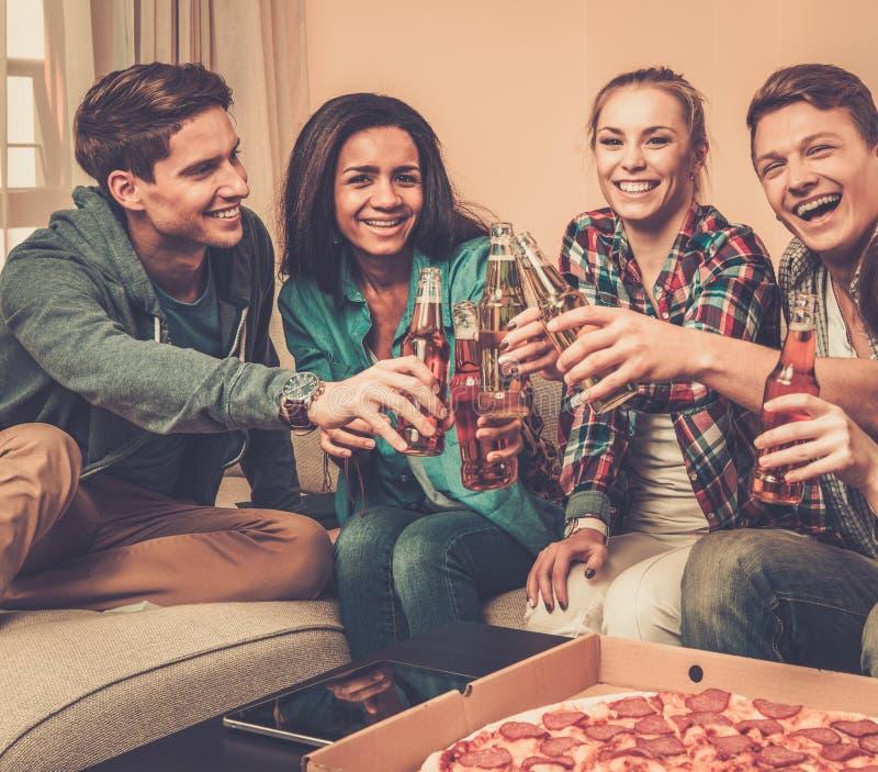 Друзья с пиццей и бутылками пить имея партию стоковое изображение