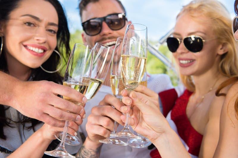 Друзья с улыбкой выпивают шампанское на яхте стоковые изображения rf
