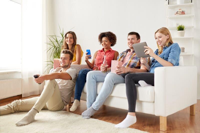 Друзья с устройствами и пивом смотря ТВ дома стоковое изображение rf