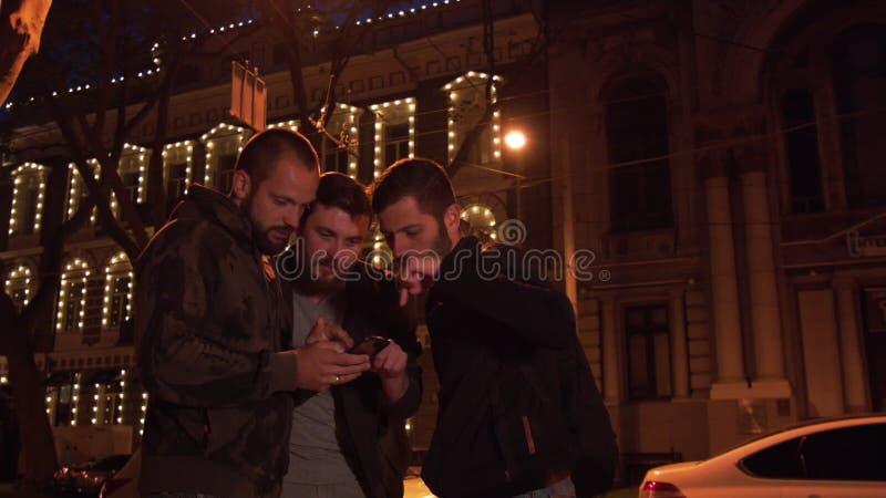 Друзья с smartphone ищут место в городе ночи Потеряла группу в составе туристы акции видеоматериалы