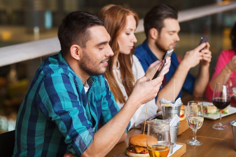 Друзья с smartphones обедая на ресторане стоковая фотография