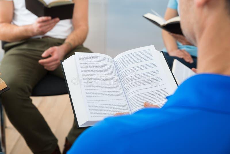Друзья читая библию стоковое изображение rf