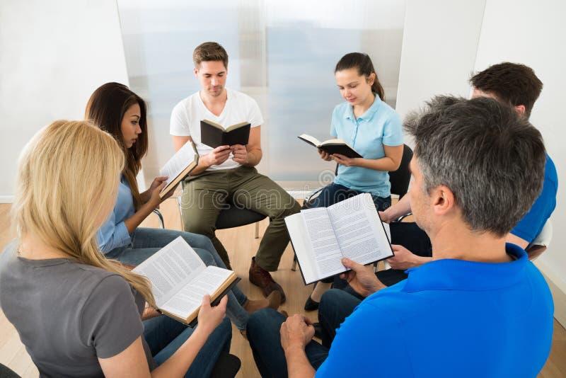 Друзья читая библию стоковое фото rf