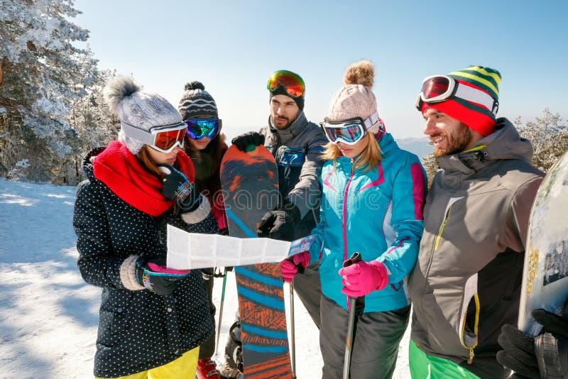 Друзья читая бумажную карту в зимних отдыхах в снежной горе стоковое изображение