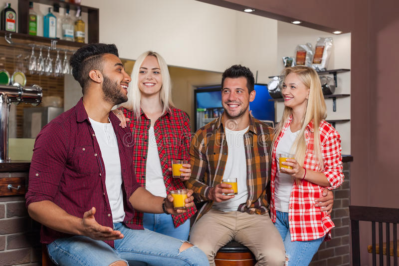 Друзья людей выпивая сидеть апельсинового сока говоря смеясь над на счетчике бара, человеке гонки смешивания и парах женщины стоковые изображения rf