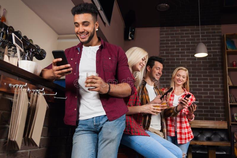 Друзья людей используя телефон клетки умный, выпивая сидеть апельсинового сока говоря смеясь над на счетчике бара, человека гонки стоковое фото rf