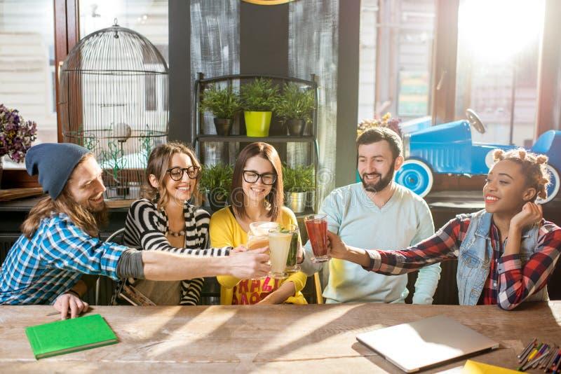 Друзья clinking стекла в современном кафе стоковое изображение