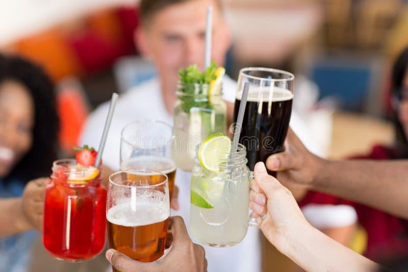 Друзья clinking стекла на баре или ресторане стоковое фото rf
