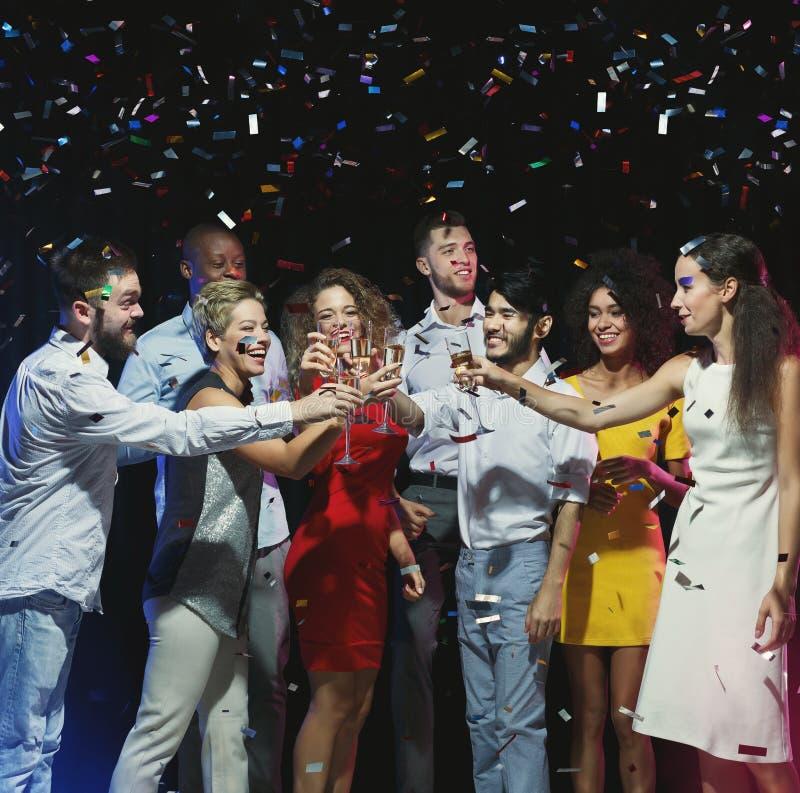 Друзья clinking стекла на партии Нового Года стоковые фотографии rf