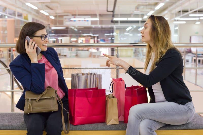 2 друз женщины сидя в моле после ходить по магазинам, смотрящ сумки, отдыхая стоковые фото