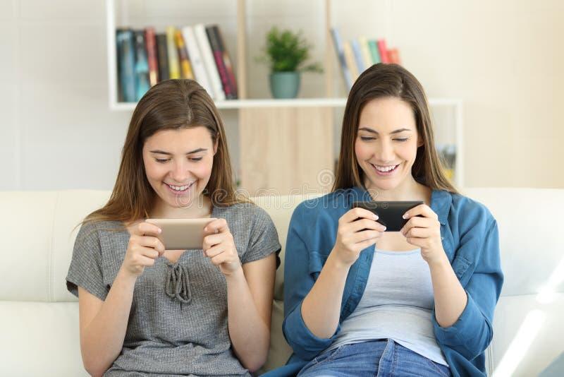 2 друз играя Онлайн-игры с smartphones стоковое изображение rf