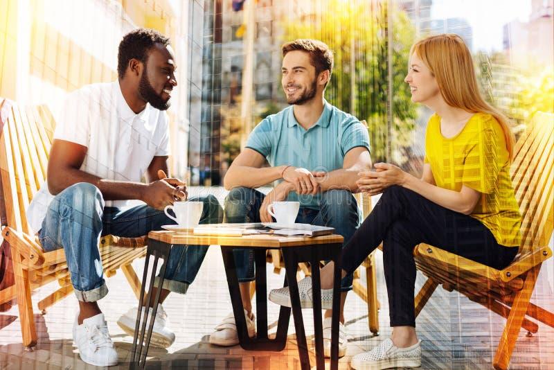 3 друз сидя на таблице с чашками кофе и говорить стоковое фото rf