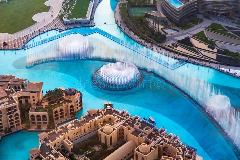 Дубай, Объениненные Арабские Эмираты - 5-ое июля 2019: Взгляд сверху шоу фонтана торгового центра Дубай окруженный и современный  стоковые фото