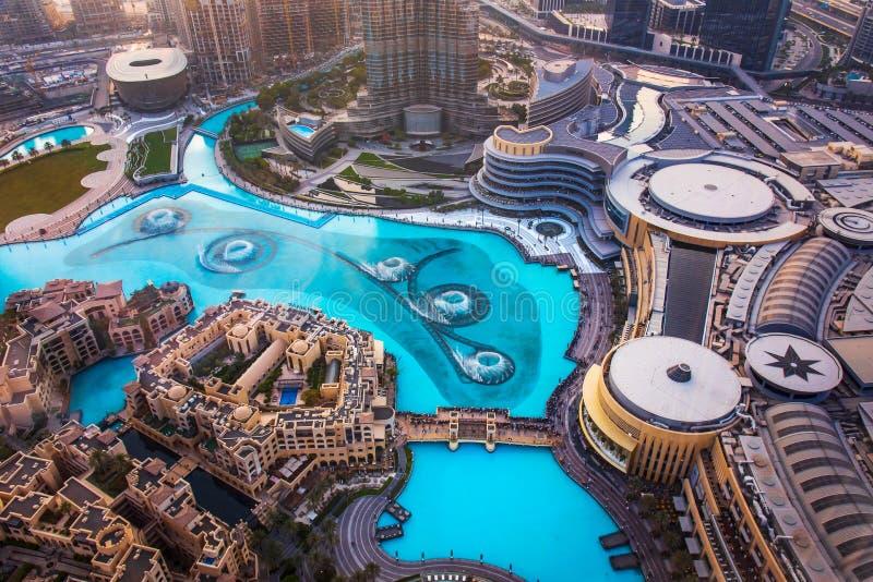 Дубай, Объениненные Арабские Эмираты - 5-ое июля 2019: Взгляд сверху шоу фонтана торгового центра Дубай окруженный и современный  стоковые фотографии rf
