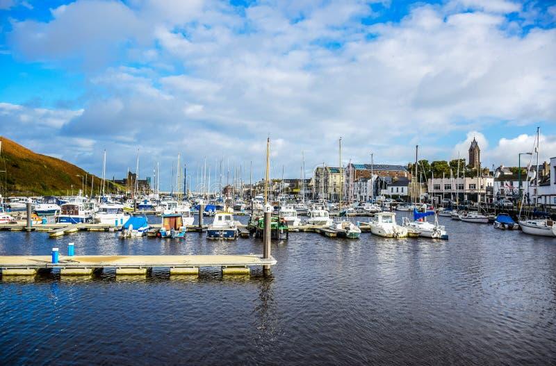 ДУГЛАС, ОСТРОВ МЭН - 17-ОЕ ОКТЯБРЯ: Плавать стыковка на заливе в славном малом порте в ясном дне голубого неба в маленьком городе стоковое фото