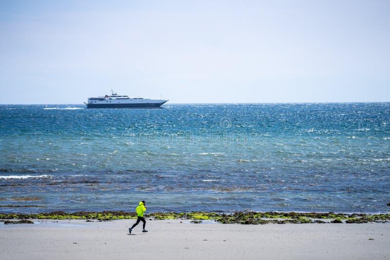 Дуглас, остров Мэн Ход человека на пляже с туристическим судном близко к берегу Сильная тренировка бегуна на открытом воздухе на  стоковое изображение rf