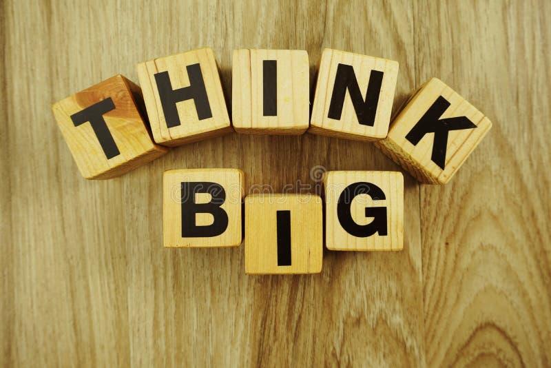 Думайте большое слово сделанное из деревянных кубов с алфавитом писем стоковые изображения