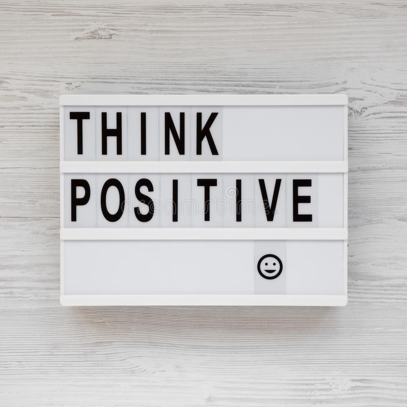 'Думайте положительно' слова на современной доске, буфер с пустым листом бумаги на белом деревянном фоне, вид сверху Накладные ра стоковая фотография