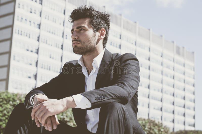 Думать молодого и красивого бизнесмена сидя стоковые изображения