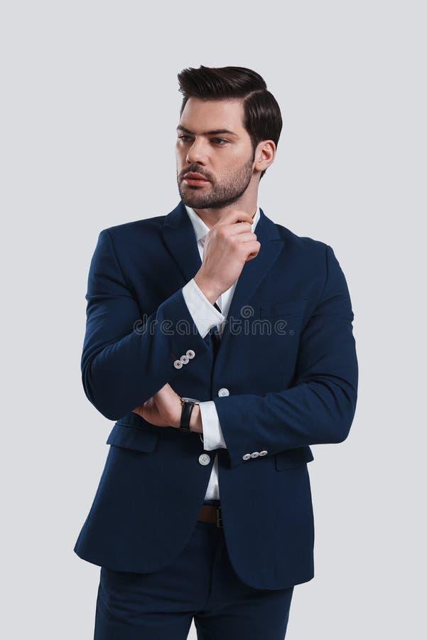 Думать около Красивый костюм молодого человека полностью смотря отсутствующий w стоковые фотографии rf