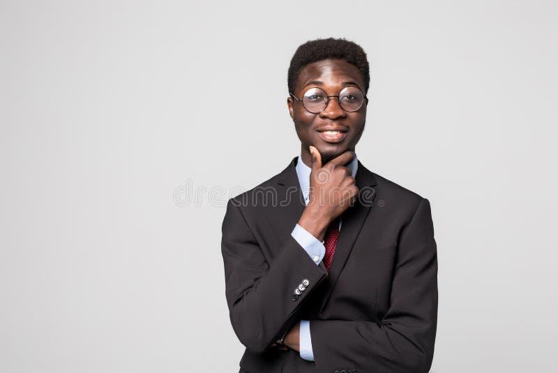 Думать о новых решениях Красивый молодой африканский человек держа руку на подбородке и смотря на камере с улыбкой на сером цвете стоковое изображение