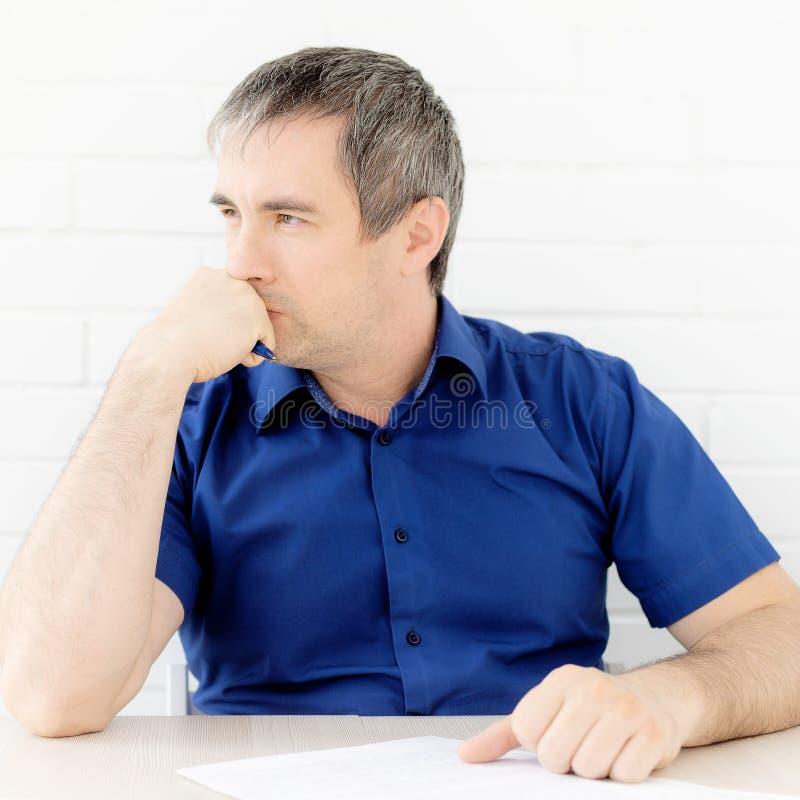 Думая бизнесмен касаясь его голове держа документ сидя на таблице стоковые изображения rf