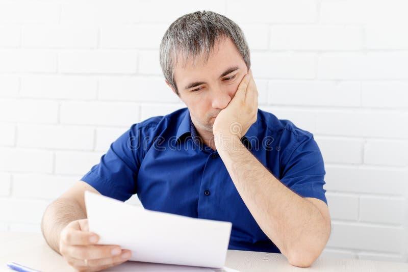 Думая бизнесмен касаясь его голове держа документ сидя на таблице человек в одеждах дела сидя на таблице и стоковые изображения rf