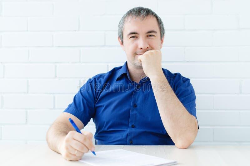 Думая бизнесмен касаясь его голове держа документ сидя на таблице человек в одеждах дела сидя на таблице и стоковое фото rf