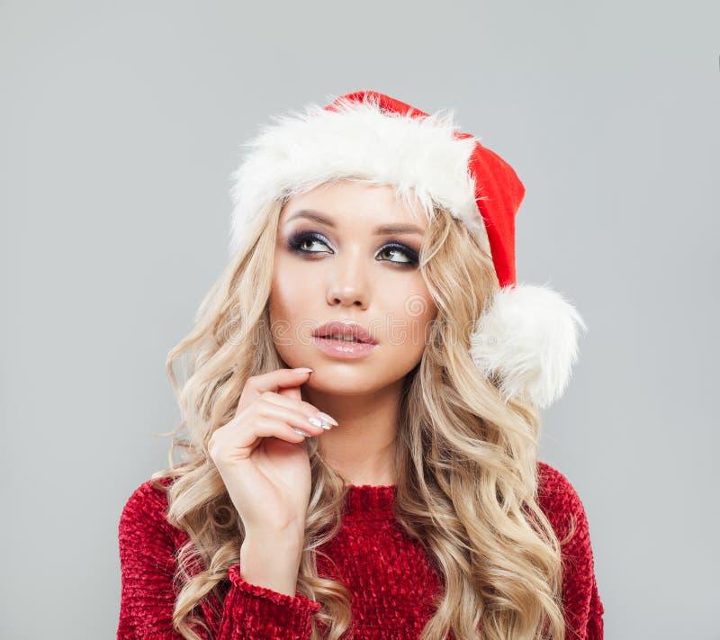 Думая женщина в шляпе santa смотря вверх Новый Год рождества стоковые фото