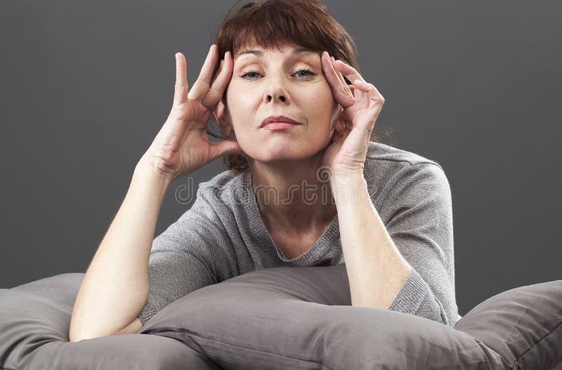 Думая женщина 50's поднимая ее глаза для мягкого лицевого контура стоковые фото