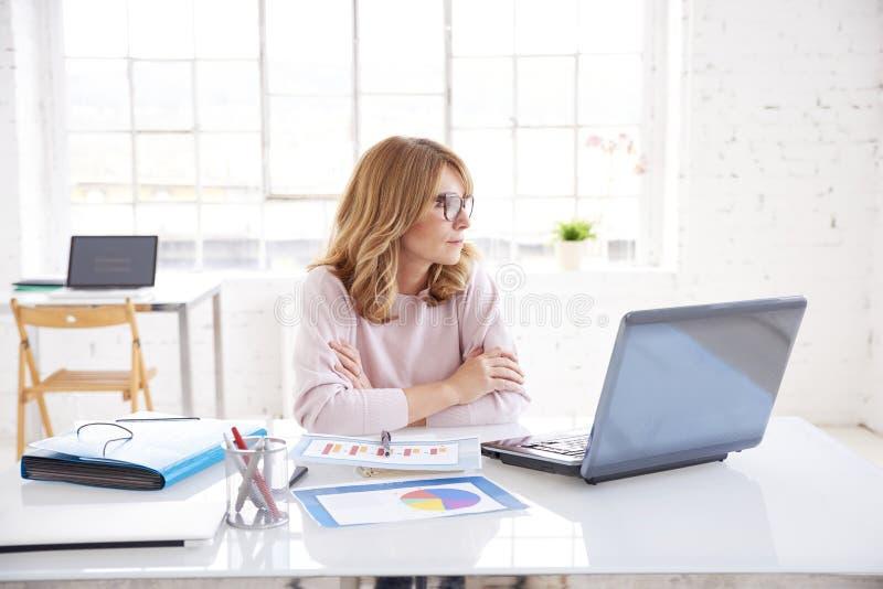 Думая коммерсантка сидя в офисе пока работающ на ноутбуке стоковые фотографии rf