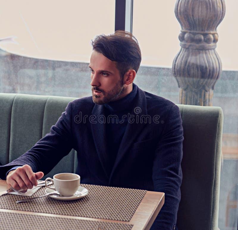 Думая красивый бородатый человек сидя в кафе и выпивая чашке кофе на к стоковые изображения rf