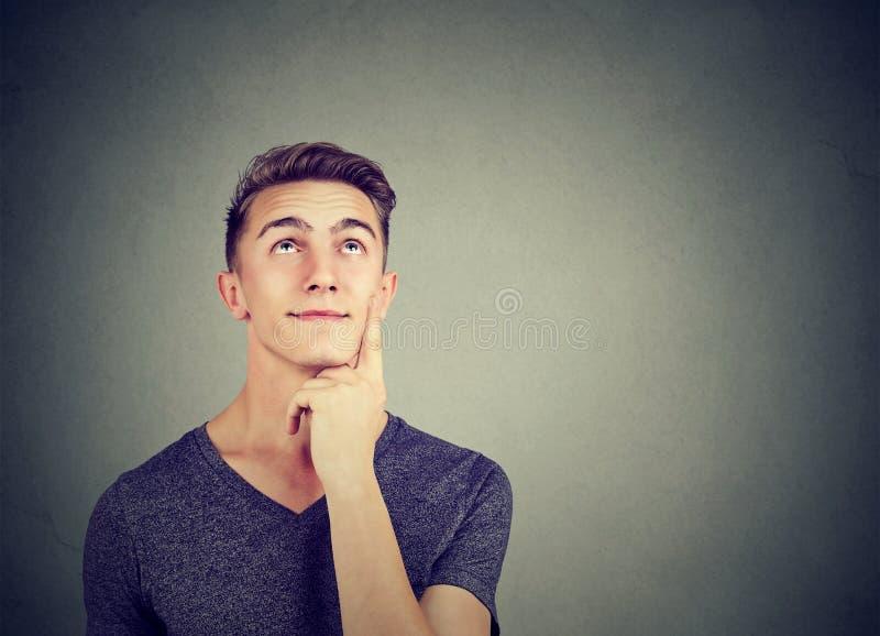 Думая молодой человек на серый daydreaming стоковые изображения