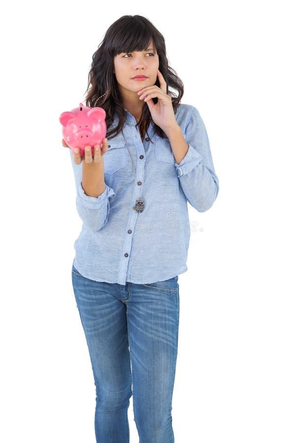 Думая молодая женщина держа ее копилку стоковая фотография