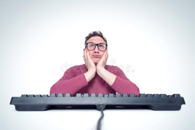 Думая человек в стеклах за клавиатурой перед компьютером, держа его голову в его руках Мечтать программист стоковое фото
