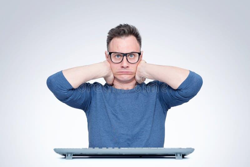 Думая человек в стеклах за клавиатурой перед компьютером смотря в камеру, держа его голову в его руках Мечтать стоковая фотография rf
