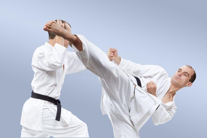 Дуновения и блоки в представлении спортсменов в karategi стоковое фото