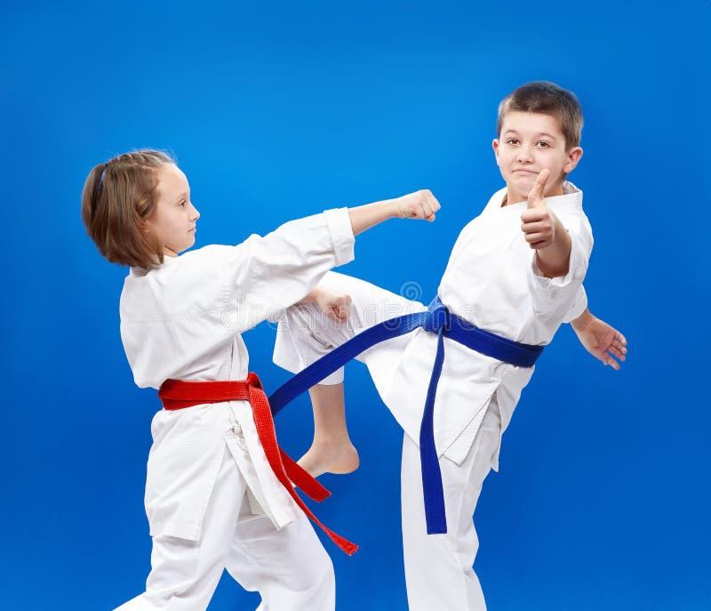 Дуновения и карате блоков тренируют детей в karategi стоковое изображение
