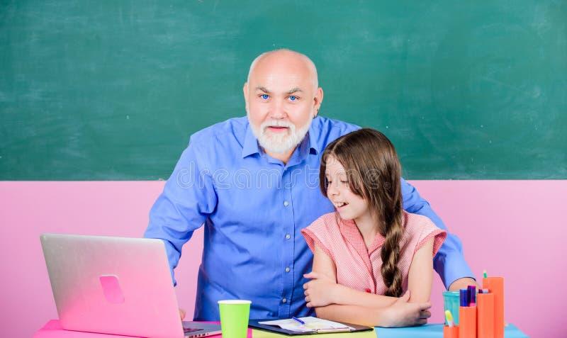 Дух школы старшая помощь учителя обучить девушку небольшая девушка с исследованием гувернера человека на ноутбуке покупки школы о стоковая фотография rf