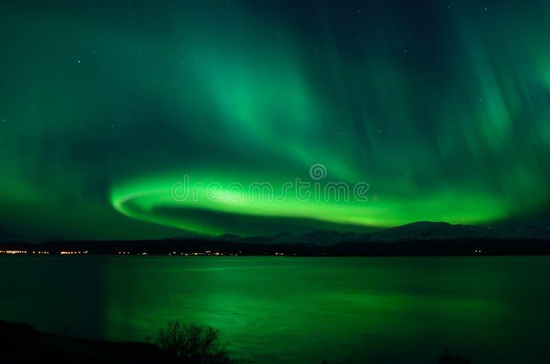 Душевнобольно сильное северное сияние над ледовитым ландшафтом фьорда и горы стоковая фотография